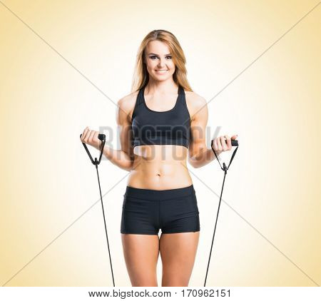 Fit, healthy and sporty woman in sportswear doing expander exercise over yellow background.