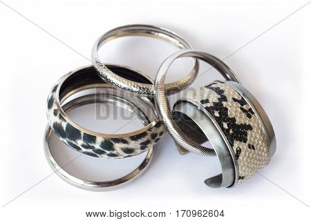 Fake snake skin and silver bracelets isolated on white background