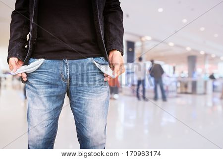 Man showing his empty pockets on blur shopping mall background.