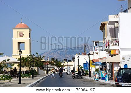 IERAPETRA, CRETE - SEPTEMBER 18, 2016 - View along a town shopping street with the clock tower to the left Ierapetra Crete Greece Europe, September 18, 2016.