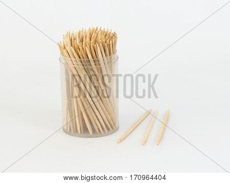 Many toothpicks in a clear plastic box on a white background.