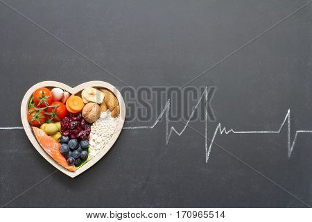 Healthy food in heart and cardiograph on blackboard medical abstract concept