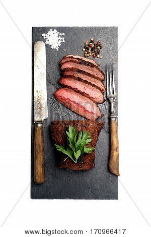 grilled steak on a black slate, knife and fork.