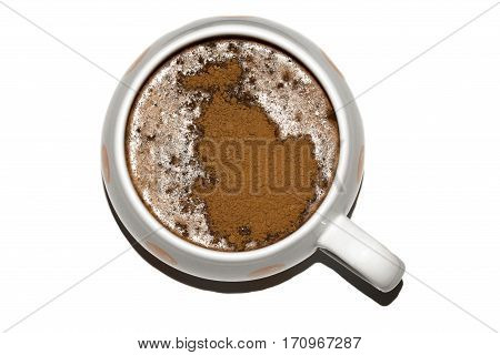 Cocoa in white mug with red dots. Drink is sprinkled with cocoa. The sprinkle has shape of fish.