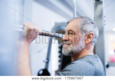 Fit senior man in sports clothing in gym working out, doing pull-ups on horizontal bar.