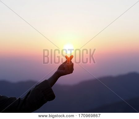 Silhouette woman hand showed mini heart finger symbol with sunlight and flare at sunrise nature background