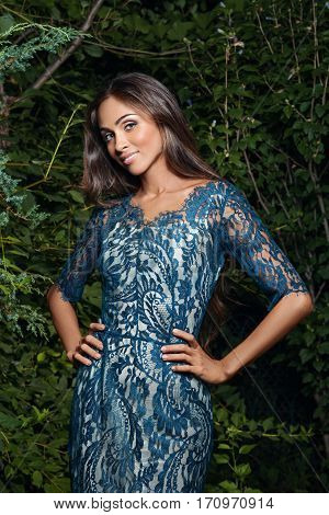 Elegant Young Woman In A Blue Lace Dress Posing Outdoors