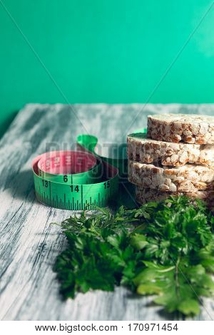 Pieces Of Crispbread Near Measuring Tape And Green Arugula On Grey Background. Diet Concept. Healthy