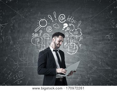 Portrait of a bearded man in a suit holding his laptop and standing near a blackboard with an internet search sketch on it.
