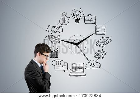Side view of a young businessman wearing glasses and thinking while standing near a gray wall with business icons drawn on the face of a clock.