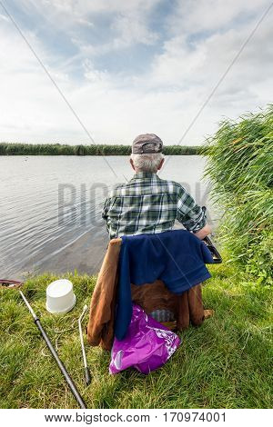 Unknown angler sitting on a chair for fishing in a small river. It's a cloudy in the Dutch summer season.