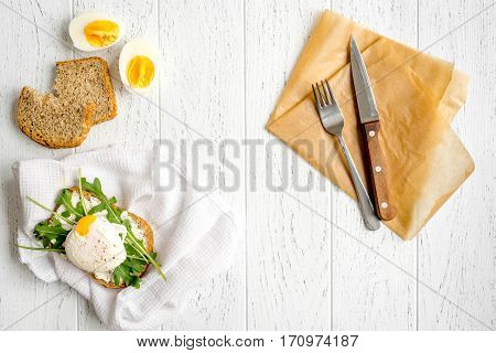sandwich with poached eggs on wooden background top view.