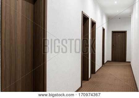 hallway with white walls closed brown door