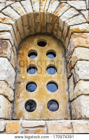 old stone window with round holes. vertical shot