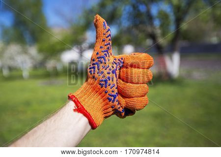 Dirty gloves on hand. Hand gesture shows everything is fine. In the background is a garden plot