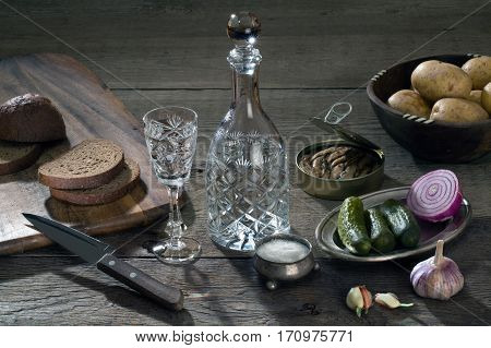 Vodka in a crystal decanter and a variety of products for snacks