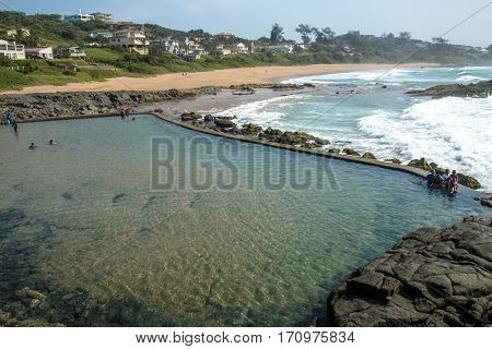 Tidal Pool Against Beach And Coastal Residential Buildings Landscape