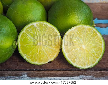 Fresh green lemon on wooden table background, Close up image