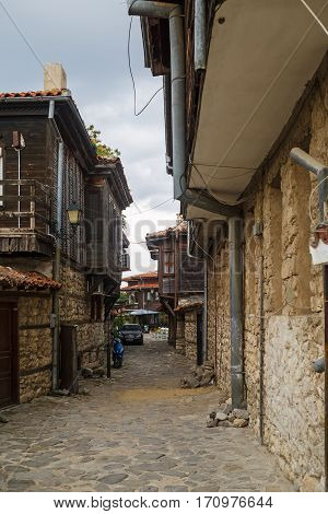 Nesebar Bulgaria - September 08 2014: Narrow street with old houses in the seaside resort and ancient old town Nessebar in Bulgaria. UNESCO world heritage site. Vertical shot.