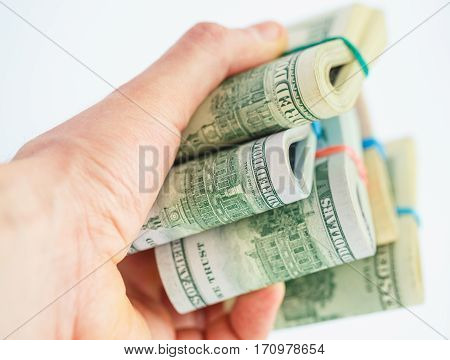 Hand holds a lot of packs with dollar bills