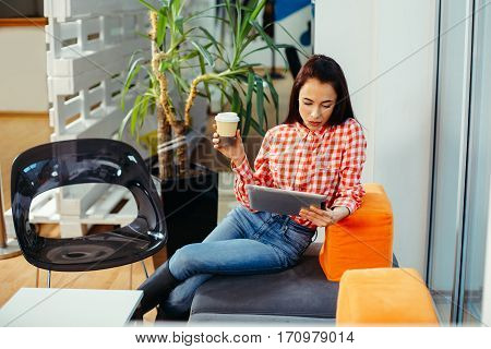 Young woman at coffee break using digital tablet in the office