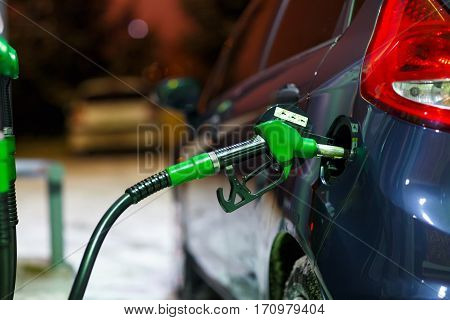 Car refueling on a petrol station in winter at night closeup