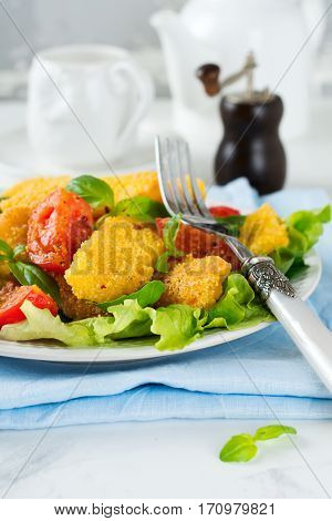Fried cheese slices in corn grits cooked tomatoes and lettuce on a light background. breakfast concept. Selective focus.