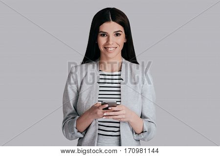 Receiving good news. Gorgeous young woman in smart casual wear using her smart phone and looking at camera while standing against grey background