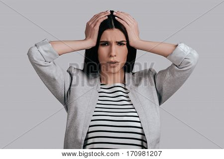 Terrible headache. Frustrated young woman in smart casual wear touching her head with hands and making face while standing against grey background