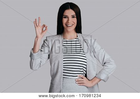 Everything is great! Beautiful young woman in smart casual wear gesturing and looking at camera with smile while standing against grey background