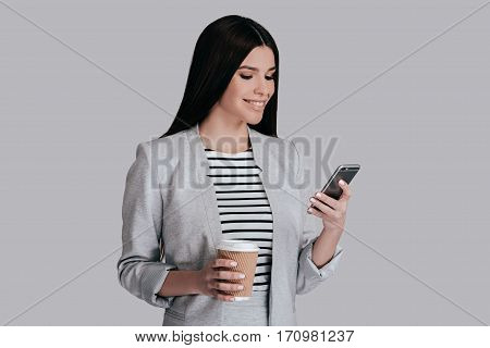 Enjoying coffee break. Gorgeous young woman in smart casual wear holding disposable cup and using her phone while standing against grey background