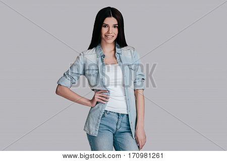 Casual and beautiful. Gorgeous young woman in casual wear keeping hand on hip and looking at camera while standing against grey background