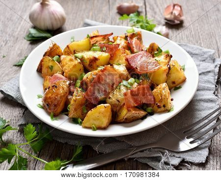 Roasted potato with bacon and green herbs on plate