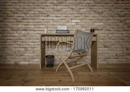 Plain desk and chair with vintage typewriter against a brick background and with hardwood floors. 3d Rendering.