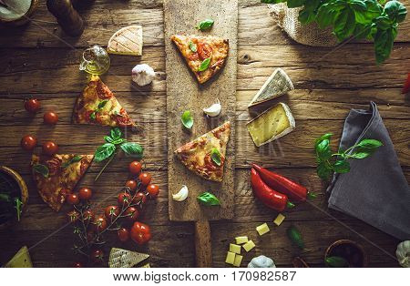 Pizza slice on wood with ingredients. Pizza with cheese tomatoes and basil. Rustic italian pizza