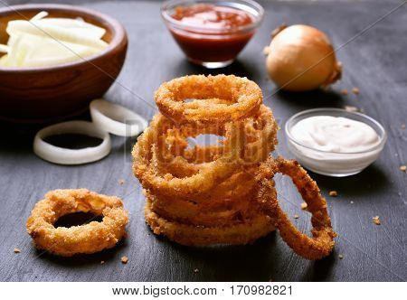 Crunchy fried onion rings and sauce on dark background
