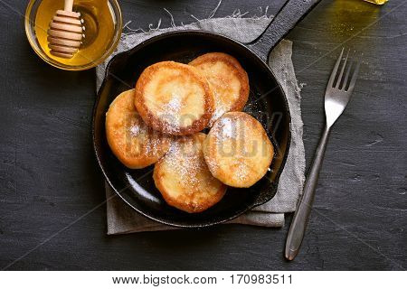 Fritters curd cheese pancakes in cast iron pan top view