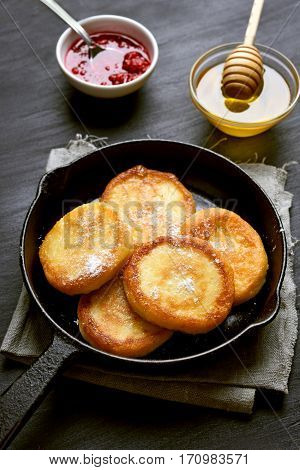 Curd cheese pancakes in frying pan on dark background