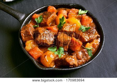 Beef stew in frying pan on balack background close up view