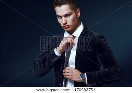 young businessman in a suit and tie on blue background