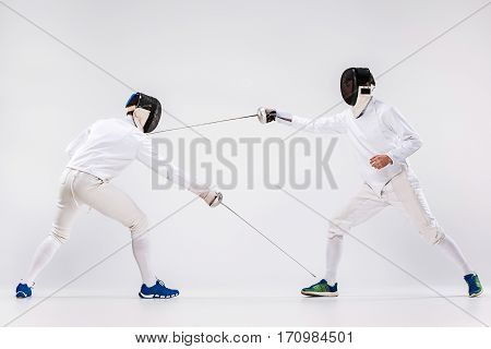 The two men wearing fencing suit practicing with sword against gray studio background