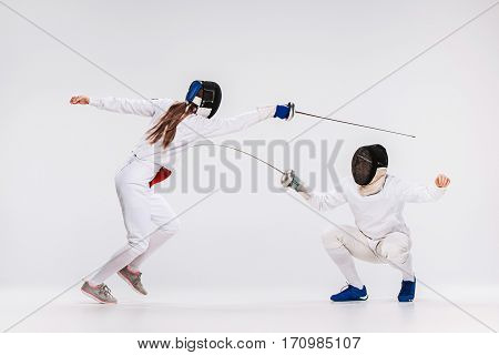 The woman and man wearing fencing suit practicing with swords against gray studio background
