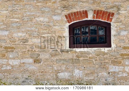 The old rock wall and a small window in the background