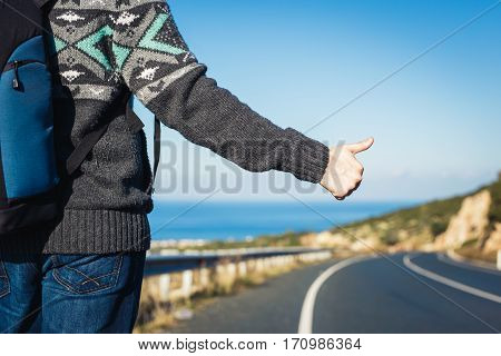 road trip travel gesture and people concept - hitchhiker stopping car with thumbs up hand sign.