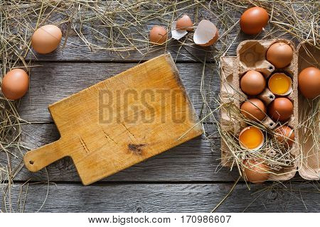 Fresh brown eggs in craft carton pack on hay at rustic wood table with wooden board for copy space. Top view. Natural healthy organic food cooking background