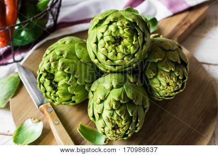 Fresh green artichokes on cutting board top view with peeled off leaves Italian sweet peppers in basket on kitchen table linen towel