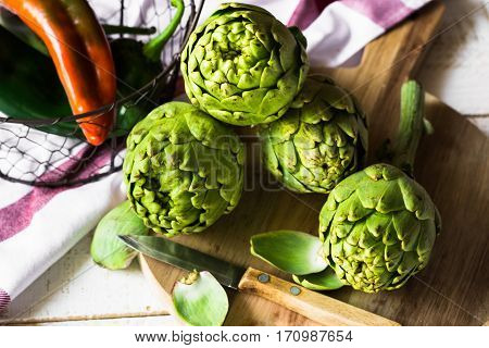 Fresh organic artichokes on cutting board peeled off leaves italian sweet peppers in basket on wood kitchen table top view