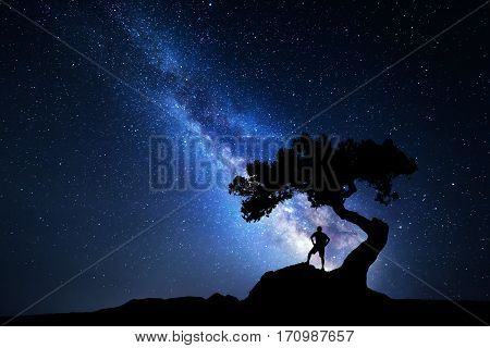 Milky Way. Night sky with stars old tree and silhouette of a standing alone man with backpack on the mountain. Blue milky way and traveler. Travel background. Silhouette of a man under the tree