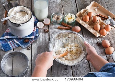 Baking concept. Flour, milk, butter, yeast and eggs carton on rustic wooden table, cooking ingredients. Unrecognizable woman's hands pov view stir dough. Female chef