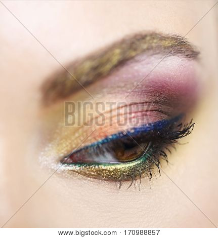 Close up portrait of a beautiful young model with bright make up. Close up of abstract multicolor make up. Makeup Pigment powder explosion